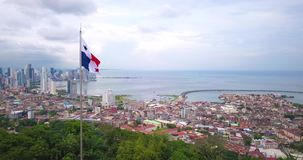 Aerial Drone view of Panama City with Flag waving. Drone flying over trees with Panama flag and view over Panama City skycrapers stock video