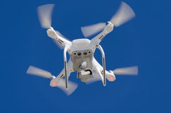 Drone flying overhead underneath bottom view against blue sky Royalty Free Stock Photo