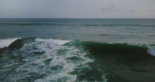 Drone flying right above big wild blue ocean waves rushing to the shore, foaming and crashing under dark cloudy sky. Drone flying right above big wild blue stock video