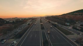 Aerial highway at sunset from drone. Drone is flying slowly toward sunset sun above big six lane two directional highway road busy with traffic and fast moving stock video