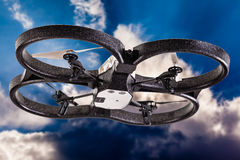Drone Flying. A small spy quad copter drone flying over a dramatic blue sky with clouds stock images