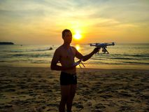 Drone flying at sunset over the sea. Man landing the drone frome the air. Sunset photo frome the air. Drone flying at sunset over the sea. Man landing the drone royalty free stock image