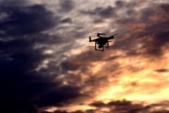Drone flying during sunset. The drone takes off as the sun sets down, giving the picture a bright orange fell with dark clouds enhancing it Royalty Free Stock Image