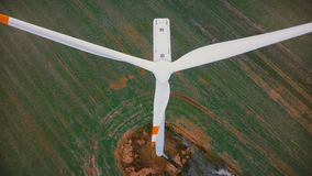 Drone flying very close up to working windmill turbine with red stripes, alternative ecological energy sources concept. stock footage