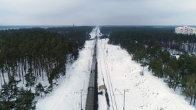 Aerial drone footage. Drone following train in winter forest. Drone following train in winter forest stock video footage