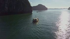 Drone Follows Tourist Boat on Tranquil Bay along Sun Path stock footage