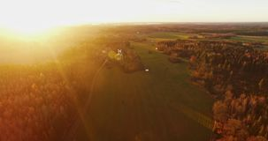 Drone footage of fields and forests at sunrise