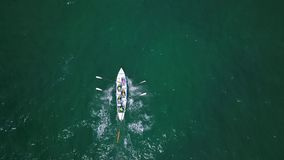 Drone footage of an ocean rowing team training in Sydney, Australia. Aerial capture of a traditional rowing team competing at sea in New South Wales, Australia stock video