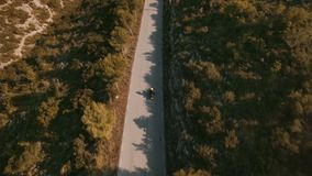 Drone footage over lonely traveler riding his motorbike on epic scenery mountain roads. Aerial shot in mountain, drone follows biker riding his motorcycle on stock video footage