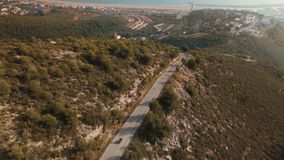 Drone footage over lonely traveler riding his motorbike on epic scenery mountain roads. Drone follows adventure traveler riding his motorcycle on epic scenery stock video