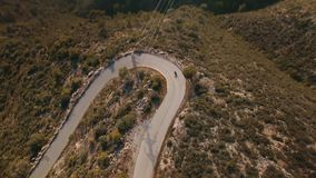 Drone footage over lonely traveler riding his motorbike on epic scenery mountain roads. Turning in big loop on serpentine, camera tilts down to top view at stock footage