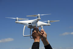 Drone in hands on blue sky. Close up drone in hands on blue sky Royalty Free Stock Photography