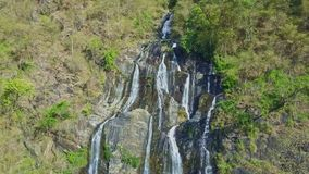 Drone Hangs above High Waterfall among Rocks in Highland. Drone hangs above high foamy waterfall with different streams among rocks in wild tropical forest stock footage