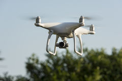 Drone hovering on the edge of woods Royalty Free Stock Image