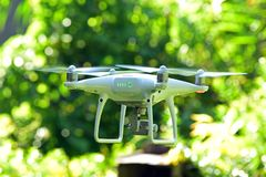 Drone hovering on green bokeh background Stock Photos