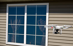 Drone hovering by house window Royalty Free Stock Photo
