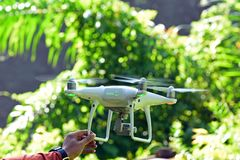 Drone hovering on man hand with green bokeh background Royalty Free Stock Photography