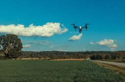Drone. Hovering over a field in the country alongside the road. With Carolina blue skies and puffy white clouds. Landscape Stock Photos