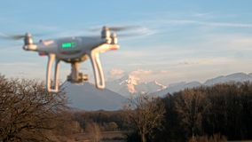 A drone hovers in flight in front of the mountains of the alps in France. stock image