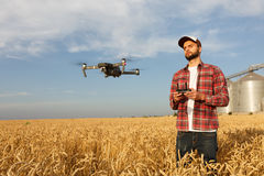 Drone hovers in front of farmer with remote controller in hands near grain elevator. Quadcopter flies near pilot Royalty Free Stock Photos