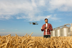 Drone hovers in front of farmer with remote controller in hands near grain elevator. Quadcopter flies near pilot. Agronomist taking aerial photos and videos in Royalty Free Stock Image