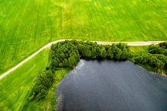Drone image. A view from above on a natural lake, road and field. Drone image of countryside. A view from above on a natural lake, road and meadow Stock Photos