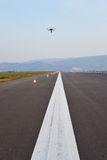 Drone inspection over airport runway. Drone over airport runway with operator at sunset royalty free stock photos