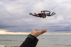 Drone landing on hand at Baltic Sea Stock Photos