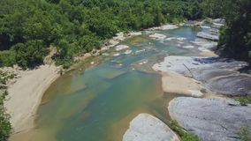 Drone Lows down and Flies above Rocky River among Jungle. Drone lows down and flies above beautiful rocky mountain river with transparent blue water among lush