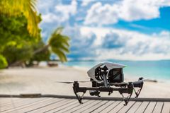 Drone making video footage and taking photographs on a tropical beach scene. Professional drone taking footage and images on a tropical landscape background Royalty Free Stock Photography