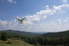 Drone with mounted camera. Flying quadrocopter drone over meadows Stock Image