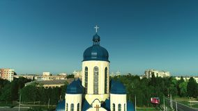 Aerial elevating up over a church with blue domes. 4K. stock video footage