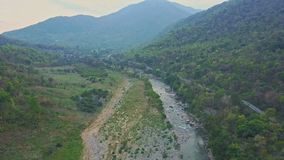 Drone moves above green river against hilly landscape blue sky. Drone moves above long green river against hilly landscape and clear blue sky in countryside stock video footage