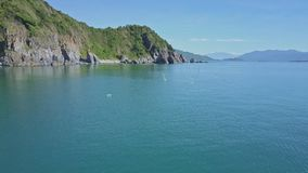 Drone Moves along Fishing Nets in Ocean to Hilly Coast. Drone moves along long fishing nets with bottles in tranquil blue ocean to green hilly coast against blue stock footage