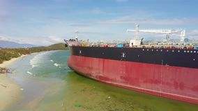 Drone Moves Close to Aground Tanker Poop in Shallow Water. Drone moves close to huge tanker poop aground on transparent ocean shallow water by beach with rubbish stock video footage