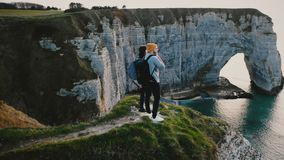 Drone moving around young happy friends standing together on top of sunset white coast cliff in Normandy watching view. Peaceful man and woman enjoying stock footage