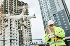 Drone operated by construction worker on building site. Construction worker piloting drone at building site. video surveillance or industrial inspection Royalty Free Stock Images