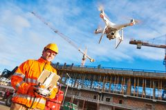 Drone operated by construction worker on building site Stock Photo