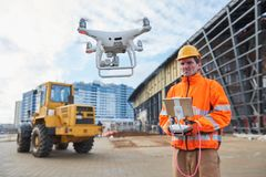 Drone operated by construction worker on building site. Construction worker piloting drone at building site. video surveillance or industrial inspection Royalty Free Stock Photos