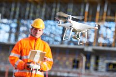 Drone operated by construction worker on building site. Construction worker piloting drone at building site. video surveillance or industrial inspection Stock Images