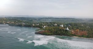 Drone panning right above amazing exotic tropical beach, seafoam waves, buildings among trees and construction site. Drone panning right above amazing exotic stock video footage