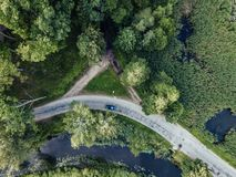 Drone Photo of Car Driving on the Road by the River under the Trees, Top Down View in Early Spring on Sunny Day - Concept of. Peaceful Life in Countryside and royalty free stock photos