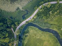 Drone Photo of Car Driving on the Road by the River under the Trees, Top Down View in Early Spring on Sunny Day - Concept of. Peaceful Life in Countryside and stock images