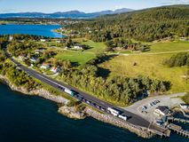 Drone Photo of the Cars Waiting in Line on Ferry Port in Langfjorden in Norway on a Sunny Summer Day with Mountains and Blue Skies. In the Background - Concept royalty free stock photos