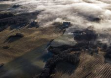 Aerial photo of foggy farmlands. A drone photo of a farmland with fog over the landscape stock image