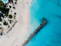 Drone photo of pier in beach in Grace Bay, Providenciales, Turks. Drone photo of beach with red umbrellas in Grace Bay, Providenciales, Turks and Caicos Royalty Free Stock Images