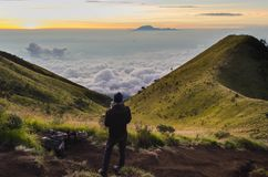 A drone pilot is flying quadrocopter on the mountain above the clouds. Sunrise at mount Merbabu, Indonesia, above the clouds. royalty free stock photography