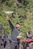A drone pilot prepares to catch a descending drone quad chopter about to land still in flight. Royalty Free Stock Image