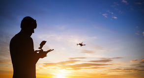 Drone pilot with quadrocopter. Silhouette against the sunset sky Stock Photo