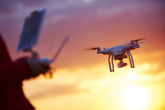 Drone pilotage at sunset. Piloting flying copter drone at sunset Stock Photo